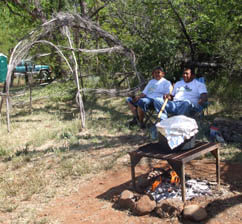 Yavapai-Apache, acorn stew cooking on grate over open fire at agave roast.