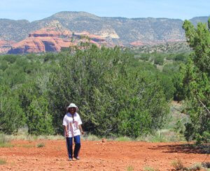 Walking with deep observing in Sedona red earth and juniper-pinyon tree landscape