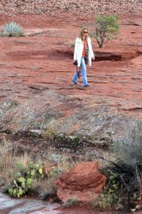 Woman walking on red rock shelf practicing nature observation during a Sedona outdoor seminar.