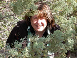 Woman smiling sitting under juniper tree--enjoyng the connection.