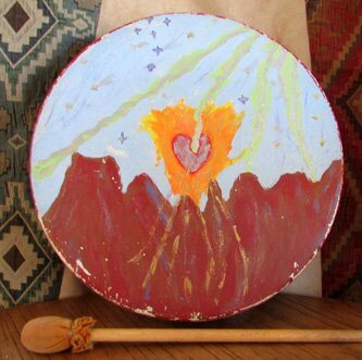 Shamanic journey drum painted with red cliffs, the sun with a heart in the center and rays of light flowing down from above. Symbolizes connections with Spirit.