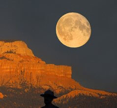 Full moon rising over red cliff, man in hat silhoutted in front of red cliffs. This represents Sedona full moon circle, journey to the drum to the drum to connect with helper spirits