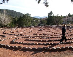 Person walking a 7 path labyrinth with mountains in background. Vision quest and ceremony, to be successful, require powerful focused attention skills.