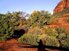 Shadow of a person exploring red rock shelf area of Sedona. Symbolizes exploring in nature spiritual practice.