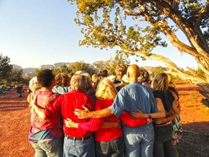 Circle of people with arms connecting each other near Sedona, Arizona. This illustrates joyous connection with the natural life forces during a solar eclipse.