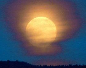 Full moon Sedona rising in cloud against dark blue sky during a full moon circle.