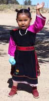 Hopi girl in traditional dress waving; symbolizes the invitation to spend Thanksgiving at Hopi on a Hopi independent travel journey