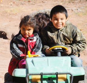 Navajo children in toy jeep in Canyon de Chelly where Navajo guides take visitors on jeep tours.