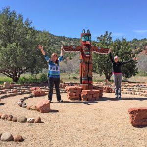 2 people arms lifted toward sky are standing next to a totem pole in center of concentric rings medicine wheel. This symbolizes the power animal activation ceremony we do during our Power Animal connections Sedona workshop.