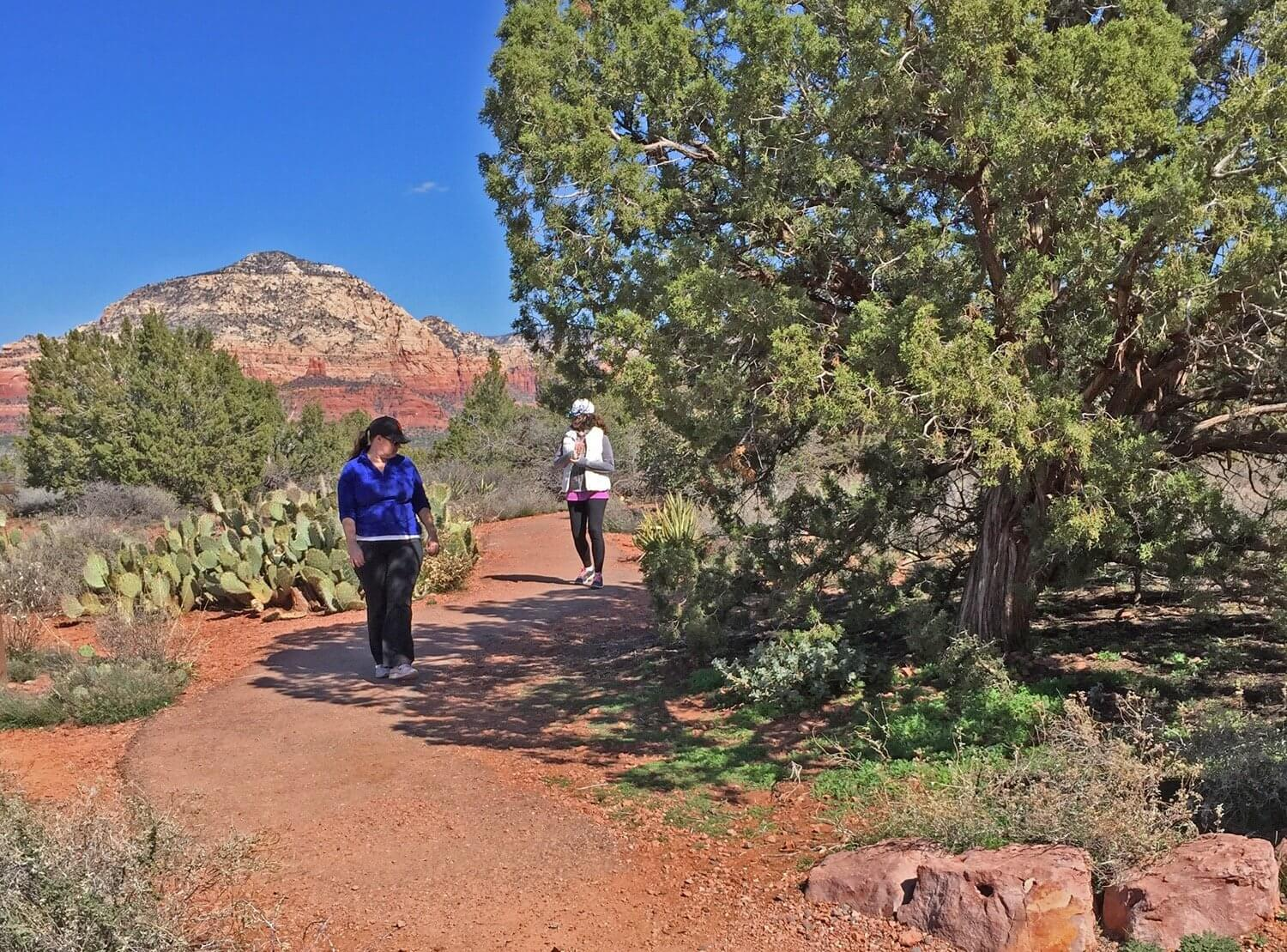 2 women walking on a red dirt trail. Shows the site where we do our sedona vortex-sacred and ancestors sites program.