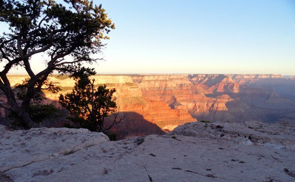First Light on rim of Grand Canyon; means our very smallness relative to the landscape is humbling.