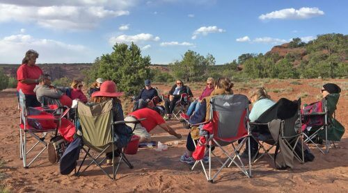 Personal circle of sharing at Canyon de Chelly with visitors seated in chairs and our Native host doing a sandpainting demonstration in center..