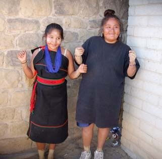 Hopi woman and girl in ceremonial costume waiting to do a youth social dance in the plaza at Hopi.