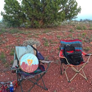 2 chairs in a Sedona red soil landscape. 1 chair contains drum which gives a feeling of being outdoors as we make mystical nature connections and do shamanic journey to the beat of the drum.