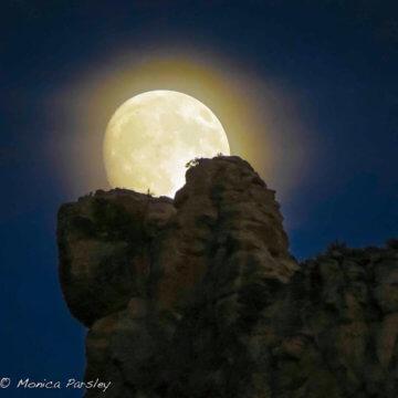 Full moon rising over cliff.